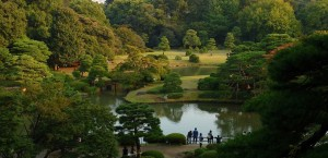 The panoramic view of the Rikugi-en Garden from the Fujishiro-toge hill vantage point. Green trees surround a serene lake. [15,16]